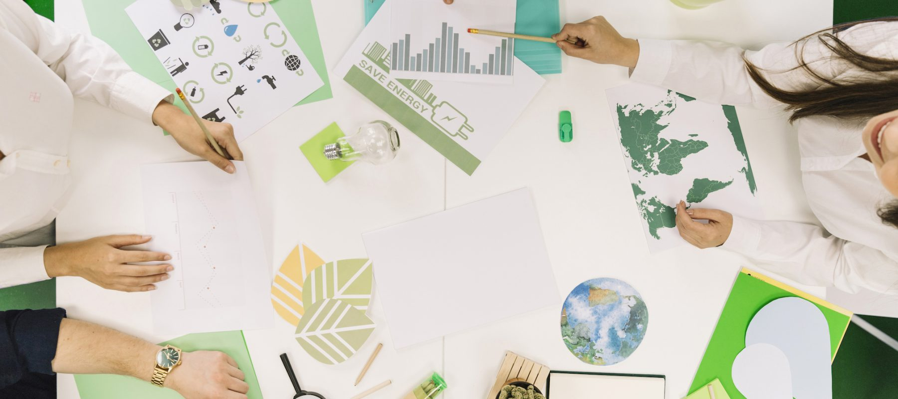 businesspeople-working-on-graph-with-various-natural-resources-icon-on-desk